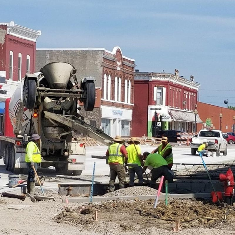 Crew works on pouring fresh concrete in street