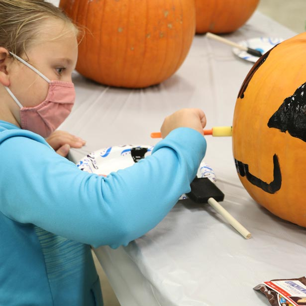 Young girl painting pumpkin at a parks and recreation event
